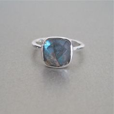 Here's a truly stunning ring. This silver ring features a large square labradorite stone in a modern cushion cut and a sleek sterling silver bezel. Stack with our other silver rings offered in a varie