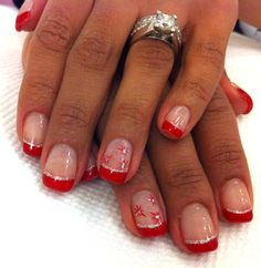 bright festive red tipped gel manicure with a thin line of silver glitter just under the red french