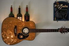 Guitar Wine Rack-- I made this out of an old, broken guitar. Didn't cost a penny. Google swirl images; print. tape Stencil on guitar. Drill holes along stencil. Remove paper. Jig saw to open top about 1/3rd down the side. inside, remove all splinters from design holes by rubbing a knife blade back n forth. Cut to fit a piece of plywood for shelf, rest on inside skeletal structure, use level, and screw in. Clean up design holes using a chain saw blade sharpener so light can shine through…