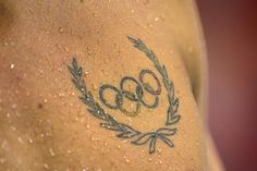 An athlete's Olympic rings tattoo is seen during a swimming event Sunday.