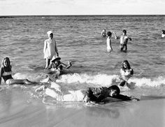 "Ringo Starr apparently doesn't lack technique, even if he does lack water, as he makes like he is swimming on the beach at Nassau in the Bahamas on April 7, 1965, while he was on location for the Beatles' latest film ""Eight Arms to Hold You."" The background is covered with Beatles, left to right, John Lennon, Paul McCartney and George Harrison, all strolling in the ocean with their clothes on. The film is scheduled for summer release through United Artists. (AP Photo)"