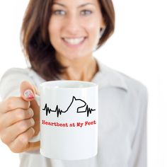 """This Funny dog coffe mugsays """"Heartbeat at my Feet"""". This awesome dog mug is the perfect gift idea for those dog lovers! Makes a great gift for friends and family who own a dog, veterinarians, vet techs, adoption shelter volunteers or directors.  Perfect coffee mug for dog lover, dog owner and puppies lover. Get one for any member of your family and use when you want to show your love for your pup.  )))  https://www.gearbubble.com/dog-heartbeat-mug"""