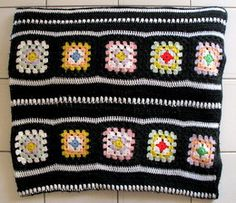 My granny square afghan pattern is worked in a variety of colors and features dividing panels incorporating a row of puff stitches.