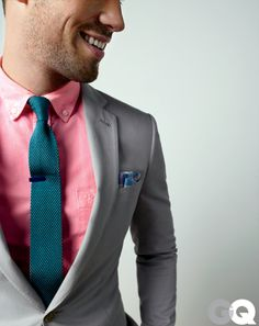 Shimmery grey and coral red against a textured tie and a tie bar.