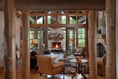Rustic Living Room with French doors, double-hung window, Hardwood floors, Columns, Casement, Fireplace, stone fireplace