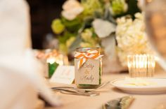 Little jars with orange and white ribbon were used for escort cards at this wedding | Photography: Chris Croy Photography | Wedding Planner: Cosmopolitan Events