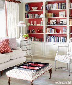 Traditional Falun red paint adds warmth and vibrancy to Swedish home's living room. The ottoman and Gustavian chair are upholstered in Schumacher's Claremont.