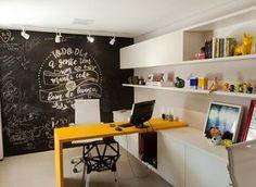 Escritório   O ambiente mais divertido do lar é o escritório. A mesa de nanoglass amarela da Carioca Granitos dá um toque especial ao cômodo, junto com a parede de lousa. Prateleiras planejadas pela Stanza Móveis (Foto: Maurício Pokemon/Divulgação )