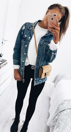 Denim jacket over white top and black skinny jeans with chic beige handbag.