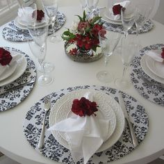 Nesta mesa usei Sousplat oval com estampa arabesco preto e branco Guardanapo barra simples branco Porta guardanapo flor pequena vermelha