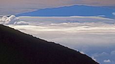 Haleakalā, or the East Maui Volcano, is a massive shield volcano that forms more than 75% of the Hawaiian Island of Maui. It is also the home of Haleakala National Park. I took this photo from the volcano's summit, looking over the clouds to a neighboring island.