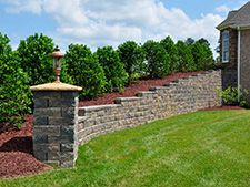 I really like the idea of planting small trees next to a retaining wall like in this example. It seems like a good way to have a barrier between your lawn and shrubs. I wonder where I could find a mason to do something like this for our house.