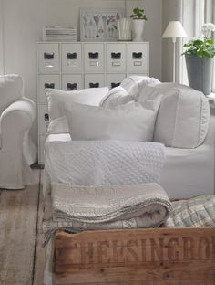 Nordic. Living area in winter, mounds of white blankets and throws.