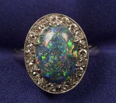 Art Deco Platinum, Black Opal, and Diamond Ring _ Sold for: $3,055 _ centering an oval opal cabochon measuring 12.80 x 8.45 x 3.30mm, surrounded by single-cut diamonds, size 5 1/4.