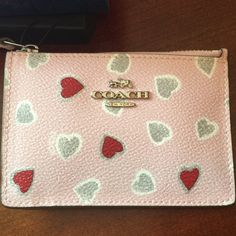"""Coach heart print ID holder- sold out online! NWT Authentic Coach mini skinny heart ID holder. Coated canvas is so cute!! Cheerful minimalist piece holds keys, cards and other small essentials in a refined, fabric-lined interior. Zip-top closure. Outside credit card pocket. ID window. 4.5""""L x 3.25""""H. Comes packaged with coach gift box. All tags attached. Sold out online. Coach Accessories Key & Card Holders"""