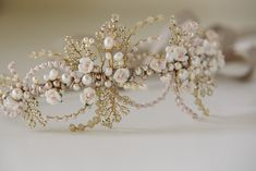 The Porcelain Rose Headdress is a beautiful asymmetrical design made from tiny little handmade porcelain roses in white and palest pink. The little roses sit amongst curves of Swarovski crystals in a very pale opaque pink and soft sand opal. Swarovski glass pearls in cream and powder almond are scattered along the band and little …