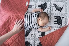 """This hand made baby quilt is truly a piece of art. Not only will you  cherish it in your nursery, in a crib or as a play mat for tummy time,but  after your little one is all grown,it will be an heirloom to hand down for  generations to come.  **MADE TO ORDER- CAN TAKE UP TO 3-4 WEEKS!**  The hand-carved block print design is made up of various land and sea  animals representing each letter of the alphabet.  All original artwork by Amelie Mancini  //  43"""" x 32""""  Width of the quilt fits…"""