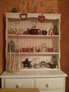 White painted welsh dresser decorated with mercury glass trees, spotted twill tape and Ikea stripped bowls.