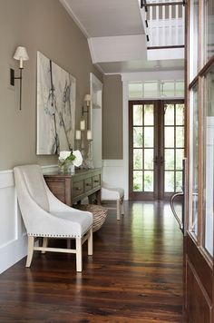 Linda McDougald Design  Beautiful entry with cafe au lait walls paint color, three-drawer console table, ivory suede Restoration Hardware Nailhead Chairs, canvas art and wall paneling.