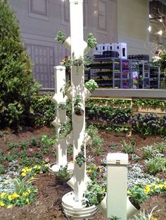 Very cool idea from Chicago's Flower and Garden show.  Vinyl fence posts with pieces if PVC pipe as pots. Top is hinged to open for watering.