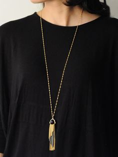 Brighton Tassel Necklace in Carbon -  INR 1,599 -  This bohemian necklace features a multi metallic tassel pendant on a golden chain. The pendant has a carbon black sphere and looks great with almost anything. You can layer this necklace with others or wear on its own. #onlineNecklace #locolatte #offer #indian #jewelry #pendant