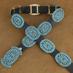 Traditional Sterling Silver Navajo Genuine Sleeping Beauty Blue Turquoise Cluster Concho Belt This Navajo Turquoise Cluster Concho Belt is an impressive piece of hand made American Indian style jewelry. This fantastic concho belt was masterfully made out of Sterling Silver. It features traditional cluster designs made from hand cut Sleeping Beauty Blue cabochons of genuine Turquoise. Turquoise jewelry is highly fashionable for its natural colors. This concho belt features a buckle and eleven…