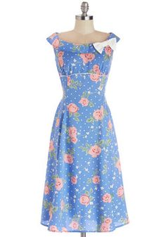 With the birds singing sweetly outside your window, this is the perfect day for this retro floral dress! The blue, polka-dotted fabric of this sleeveless dress is splashed with rose-pink flowers, and its bust is accented with white piping and a bow. When you skip down the street in your white wedges, victory rolls, and this pastel sheath, you're sure to feel positively pleasant!