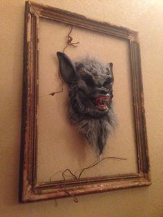 This is my favorite & so easy to create!  Hang an old frame then tack (with thumb tacks) a mask to the wall from the inside!  Danali Home for Sinister Sisters 2014.