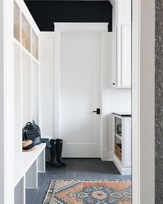 Love the black paint above the trim detail in this mudroom - it takes the entire space to the next level while still maintaining a clean and classic vibe. Builder: @timbertrailshomes Design: Julie Howard 📷:@stofferphotographyinteriors