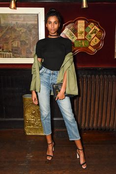 Model Imaan Hammam in a minimalist cord choker, simple black tee, khaki jacket (casually hanging off the shoulders, obvi), cropped jeans and barely there stilettos
