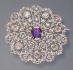 Platinum, 18k gold Edwardian brooch set with diamonds & an emerald cut amethyst.