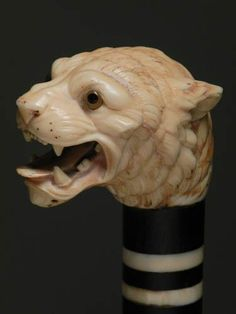 CARVED IVORY AND EBONY CAT HEAD WALKING STICK, circa 1870, aggressive cat head with glass eyes on a walrus ivory and ebony shaft, bone ferrule. L 37.5 in.