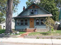 Arts & Crafts bungalow in south Broad Ripple area. Lots of charm with oak hardwoods on main level and pine hardwoods upstairs. Original stained woodwork. Fireplace in living room accented by built in bookcases. Columns between living and dining rooms. Glass enclosed porch across the front of the home. Lots of upside potential with some paint and decorating. #zillow
