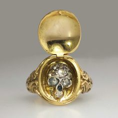 Rare 1850's Georgian Memento Mori Rose Cut Diamond Skull Locket Ring 15k/SS | Antique & Estate Jewelry | SOLD: 1/2/15 Jewelry Finds Price: $6100.00 A true museum quality ring and rare find from the late Georgian era, Circa 1850. This magnificent 'Memento Mori' ring is both a locket AND a hidden diamond skull ring. On the inside of this hidden treasure of a ring is a skull set with diamonds over an adhesive of some kind and the solid sterling silver skull