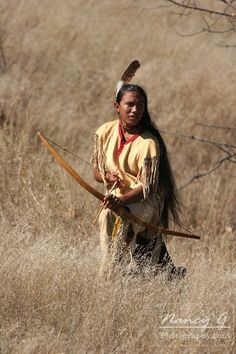 A young Native American Indian boy using and hunting with a bow and arrow
