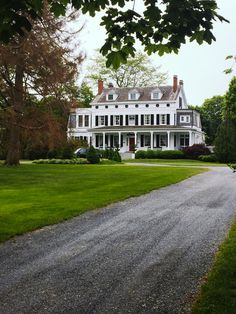 long gravel driveway, big front lawn, white colonial home.