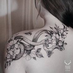 Snake, flowers and bees tattoo on the left shoulder.