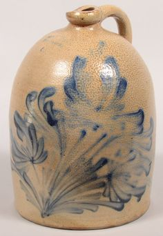"""Sold $ 1,900 M. & T. Miller, Newport, PA Tulip Decorated 3 Gallon Stoneware Jug. Circa. 1864-1877. Large cobalt blue spray of 3 tulips and foliate slip decoration. Ovoid form with molded spout and loop handle. 14 1/2"""" high. Condition: Losses to spout and two flake chips on base."""