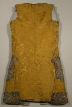Back of Waistcoat, 1750-1760, made from gold silk damask lined with cream twilled silk facings and part lining with a cream linen back. It is trimmed with silver lace 10cm deep around the front and the hem and round and on the pocket flaps. The lace is made en disposition. There are 17 buttons embroidered with silver purl and plate.