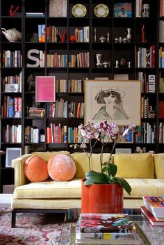 Pale yellow velvet sofa - dark built in library shelves - frames mounted on shelves - @psstudio www.pencilshavingsstudio.com