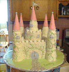 Buttercream castle cake - This is my third castle cake. I didn't deviate much from my other designs except the towers are all edible this time. The towers are stacked ice cream cones (flat-bottomed kind). Turrets are sugar cones covered in fondant. Stonework is piped buttercream. Vines are royal icing. Flowers, windows, doors and path are fondant. Grass is royal icing. I wish I'd taken a photo with a background other than my messy kitchen!