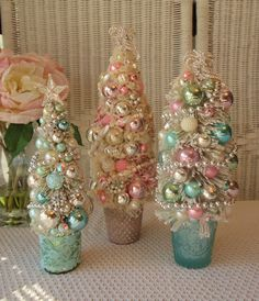 This lovely tree just sparkles with its many mercury glass ornaments in soft, dreamy shades of pink, mint, aqua and silver. I planted it in a beautiful glass base the color of aqua sea glass. Its draped with a silver beaded garland and topped with a rhinestone bow! Measures approx. 12 tall! SHIPPING: Shipping charges are based on estimated weight, box size and packing materials and therefore may vary. I try my best to refund any shipping overages that exceed $1.00. All items are packed with…