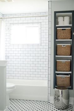 Fantastic bathroom features a drop in shower clad in white subway tiles accented with black grout ...