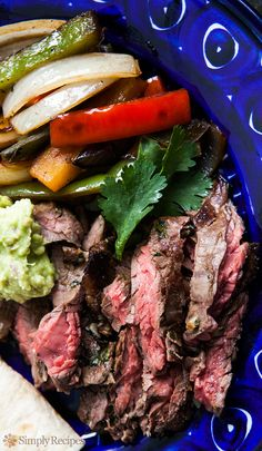 Steak Fajitas! Classic Tex Mex fajitas recipe, made with strips of skirt steak, onions and bell peppers, and served sizzling hot with fresh tortillas, guacamole, sour cream, and salsa. On SimplyRecipes.com