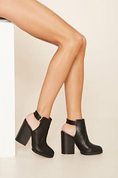 A pair of faux leather ankle booties with a buckled back strap, a rounded toe, a chunky block heel, and a cutout back design.