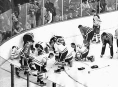 """Players of the Toronto Maple Leafs and the Chicago Black Hawks search for Jack Evans' lost contact lens during an ice hockey game, 1962."""