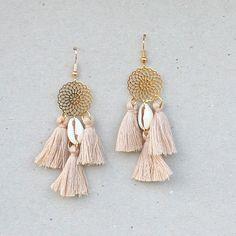 Les BO CEREN sont composées d'une estampe en métal doré (2cm de diamètre) à laquelle est suspendu un coquillage Cauris Africain accompagné de 3 pompons en coton DMC faits-main Beige (2,5cm).Longueur totale : 7cm