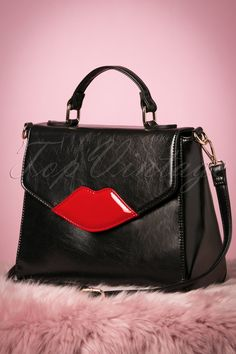 Meet your new vintage bestie! This 50s Read My Lips Bag in Black is so much more than just another bag!You can kiss my... bag! This amazing medium sized bag is made from a high quality faux leather in black that features a striking lipstick red lips application on the front. Finished off with a magnet closure and a short handle, but she also comes with a longer detachable handle, so you can wear her crossbody as well. Compliment all your retro looks with this must-have bag and take her with…