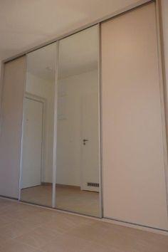 Čtyřdílná vestavěná skříň na míru se zrcadlem a s posuvnými dveřmi. Světlá barva a sklo byly použity kvůli optickému zvětšení prostoru.