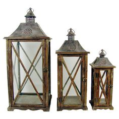 Set of three candle lanterns with distressed wood frames and glass paneling.   Product: Small, medium, and large lanternCo...